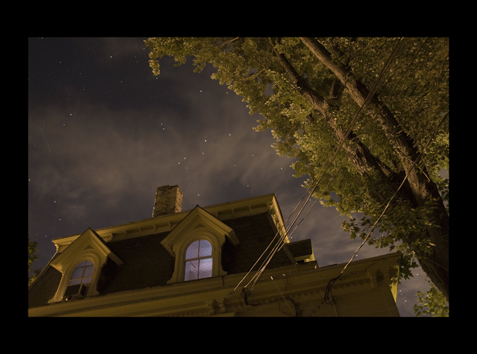 a room lit by a tv. outside tree and house theatrically lit by streetlight. stars and clouds